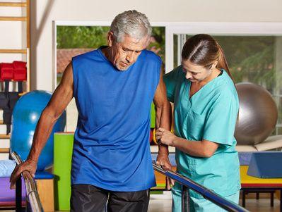 Arzthelferin hilt einem Patienten