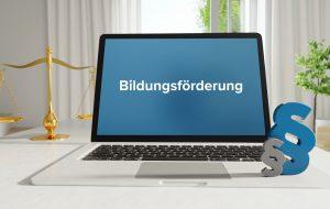 Bildungsförderung – Recht, Gesetz, Internet. Laptop im Büro mit Begriff auf dem Monitor. Paragraf und Waage.